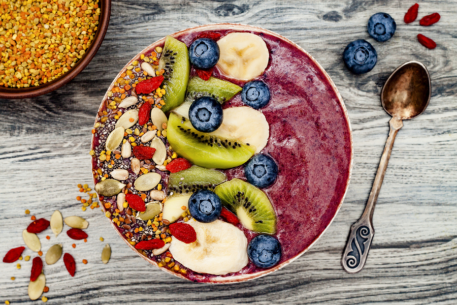 Acai breakfast superfoods smoothies bowl with chia seeds bee pollen goji berry toppings and fruits. Overhead top view flat lay